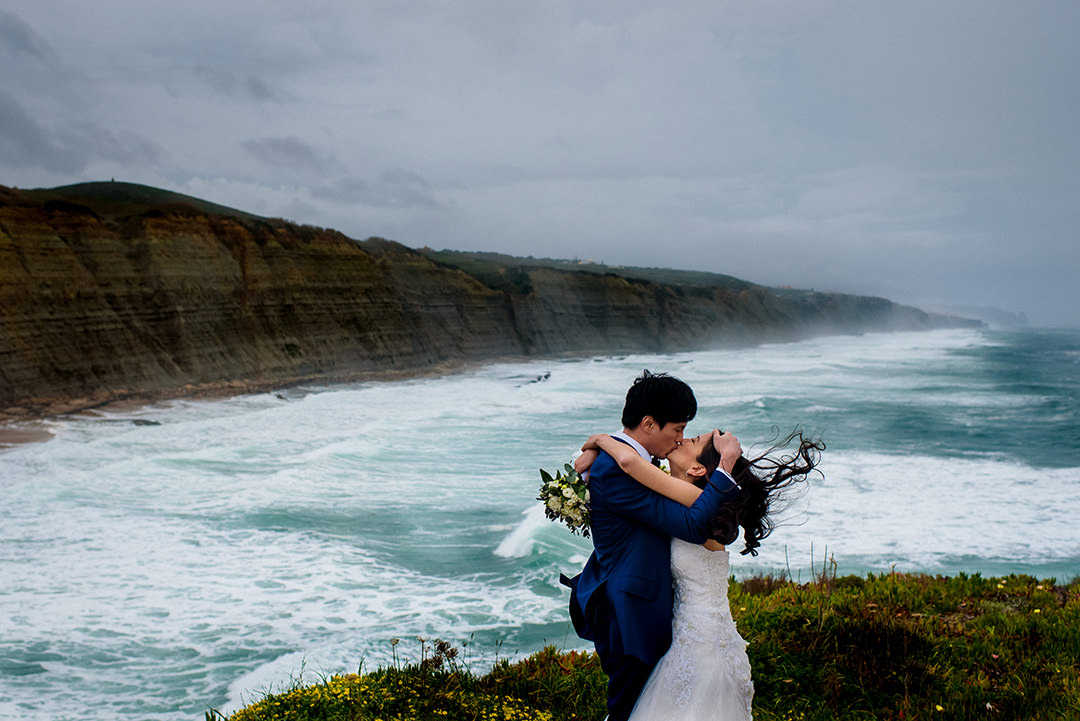 bride and groom on a lisbon windy cliff